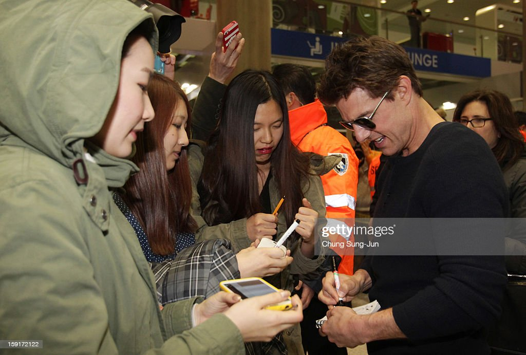 Actor Tom Cruisesigns autographs for fans as he arrives at Incheon International Airport on January 9, 2013 in Incheon, South Korea.