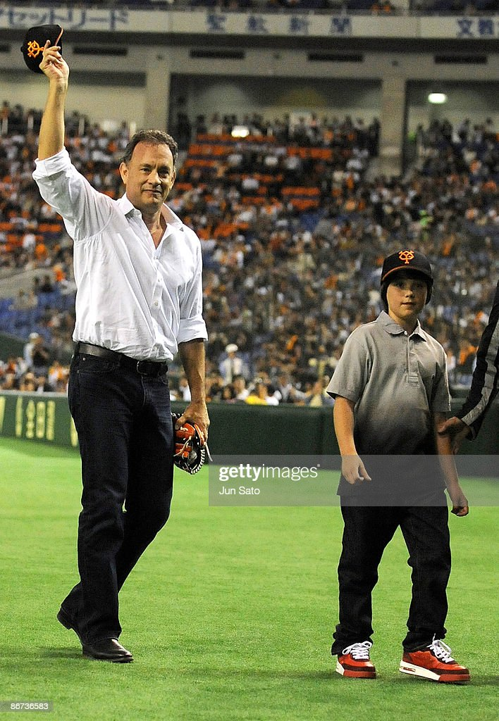 Actor Tom Hanks and Thomas Grazer gesture to the crowd during the ceremonial first pitch prior to the professional baseball match between Yomiuri...