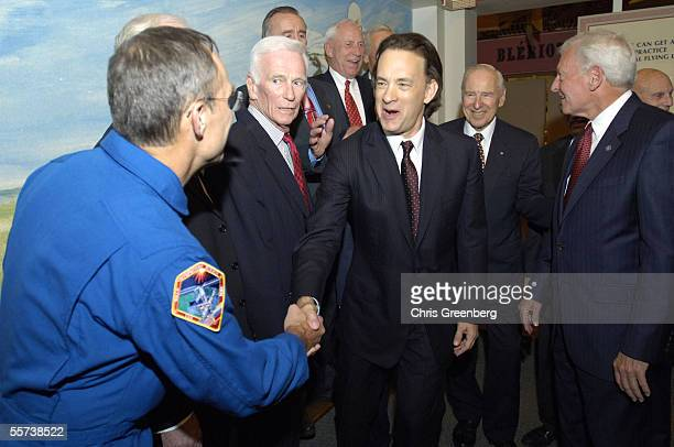 Actor Tom Hanks excitedly shakes the hand of astronaut Col Carl E Walz while a host of former Apollo astronauts look on before the screening of the...