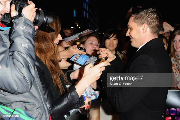Actor Tom Hardy signs autographs as he attends a screening of 'Locke' during the 57th BFI London Film Festival at Odeon West End on October 18 2013...