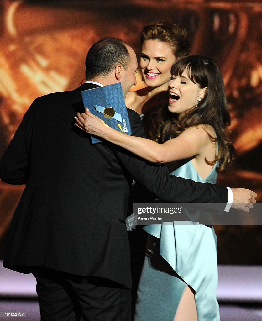 Actor Tony Hale recieves an award from actresses Emily Deschanel and Zooey Deschanel onstage during the 65th Annual Primetime Emmy Awards held at...