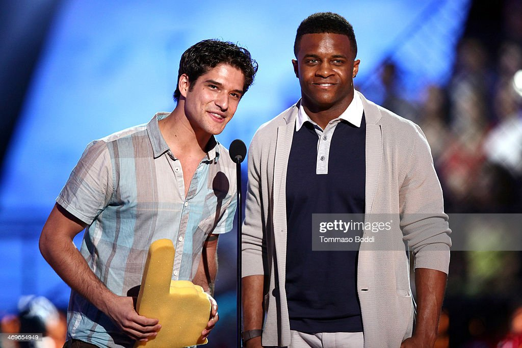 Actor Tyler Posey (L) and NFL player Randall Cobb of the Green Bay Packers speak onstage during the 4th Annual Cartoon Network Hall Of Game Awards held at the Barker Hangar on February 15, 2014 in Santa Monica, California.