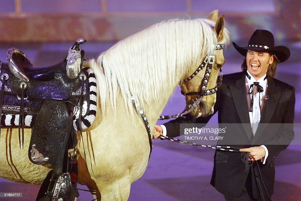Actor Val Kilmer walks out with a horse after he introduced a special segment in honor of singing cowboys Roy Rogers and Gene Autry during the 71st Academy Awards 21 March 1999 at the Dorothy Chandler Pavilion in Los Angeles, CA. (ELECTRONIC IMAGE) AFP PHOTO Timothy A. Clary