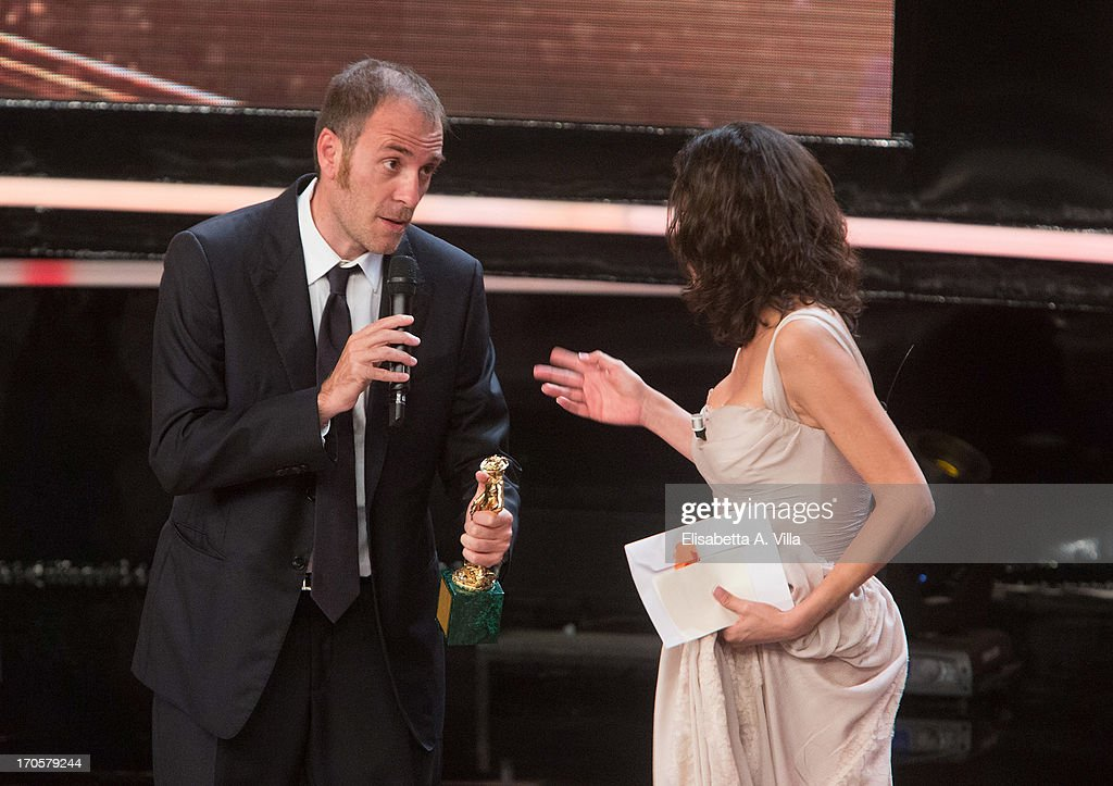 Actor <a gi-track='captionPersonalityLinkClicked' href=/galleries/search?phrase=Valerio+Mastandrea&family=editorial&specificpeople=2933889 ng-click='$event.stopPropagation()'>Valerio Mastandrea</a> receives the award for the best actor during 2013 Premi David di Donatello Ceremony Awards at Dear RAI Studios on June 14, 2013 in Rome, Italy.