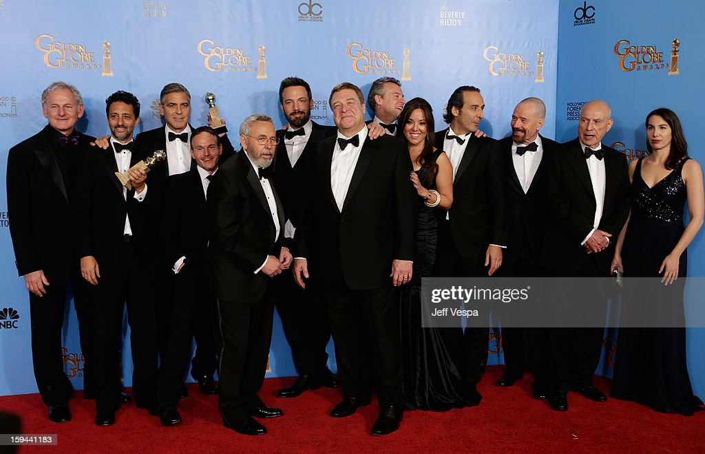 Actor Victor Garber, producer Grant Heslov, actor-producer George Clooney, former CIA agent Tony Mendez, actor-director Ben Affleck, actors John Goodman and Tate Donovan, producer Chay Carter, composer Alexandre Desplat, actors Bryan Cranston and Alan Arkin, and producer Nina Wolarsky pose in the press room at the 70th Annual Golden Globe Awards held at The Beverly Hilton Hotel on January 13, 2013 in Beverly Hills, California.