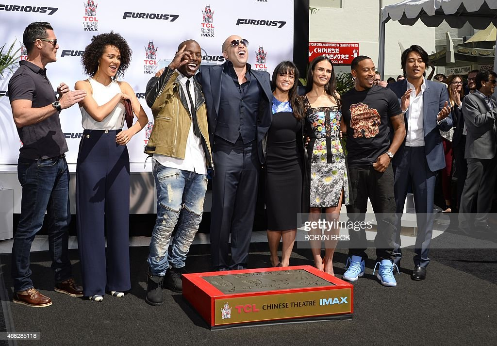 Actor Vin Diesel poses with actors Tyrese Gibson and Michelle Rodriguez and other member of the 'Furious 7' cast as he is honored with a hand and...