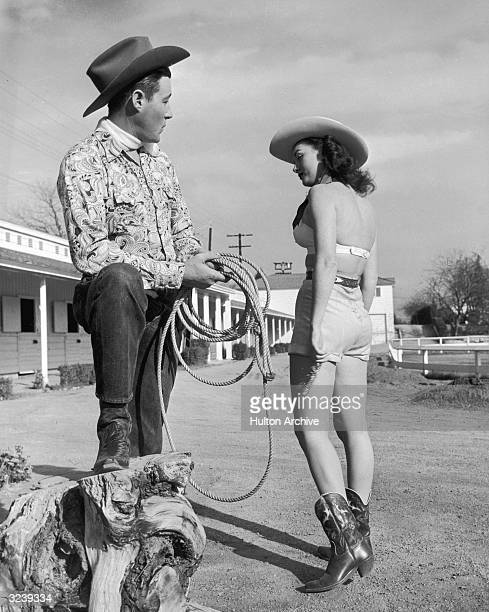 Actor Wayne Burson in a cowboy hat stands with his foot propped on a wooden stump holding a lasso and looking on with interest as actress Wendy...