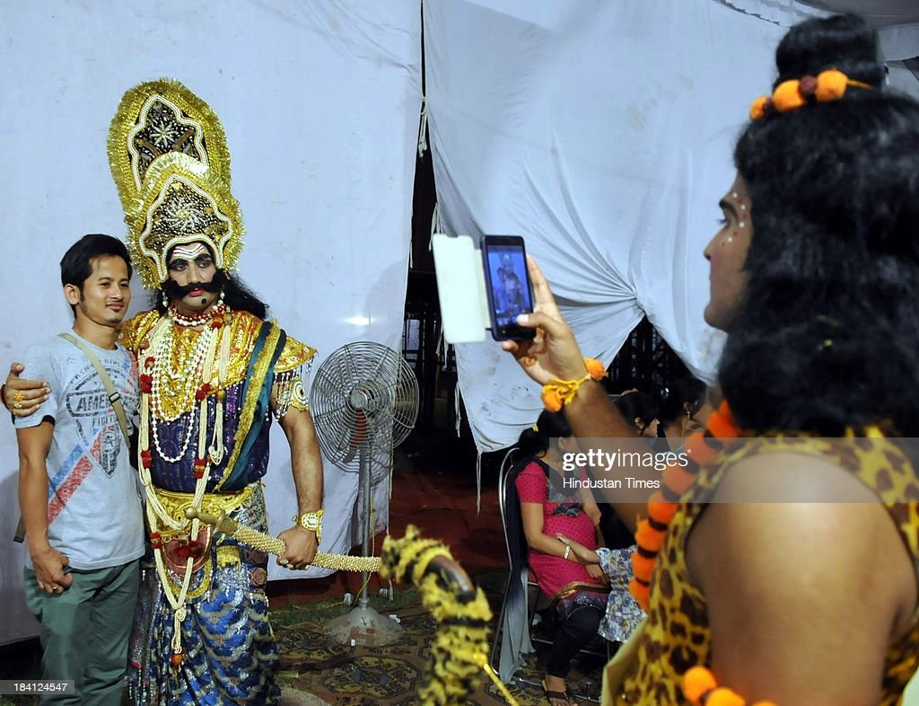 Actor who perform Lord Shiva clicking picture of Ravana on his mobile in backstage of Ramleela at Noida stadium on October 11, 2013 in Noida, India. Ramlila is a dramatic folk re-enactment of the life of Hindu Lord Rama's victory after a ten day battle with the ten headed Demon King Ravana.