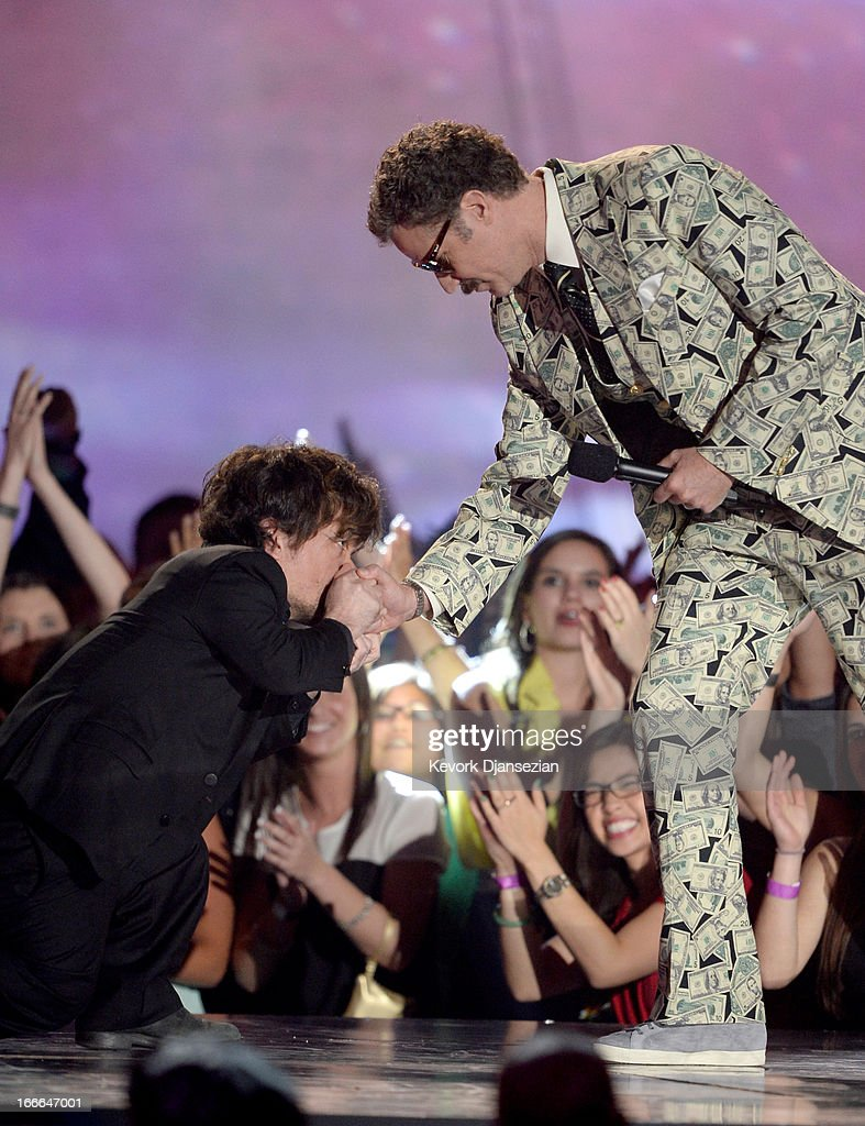 Actor Will Ferrell (R) accepts the Comedic Genius Award from actor Peter Dinklage (L) onstage during the 2013 MTV Movie Awards at Sony Pictures Studios on April 14, 2013 in Culver City, California.