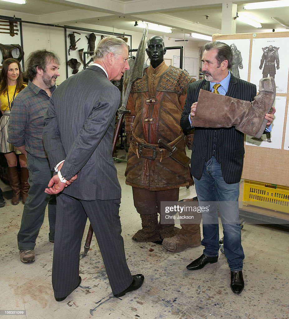 Actor William Kircher who plays 'Bifur' in the new Hobbit film shows Prince Charles, Prince of Wales a Hobbit boot as Peter Jackson looks on at Weta Workshop on November 14, 2012 in Wellington, New Zealand. The Royal couple are in New Zealand on the last leg of a Diamond Jubilee that takes in Papua New Guinea, Australia and New Zealand.