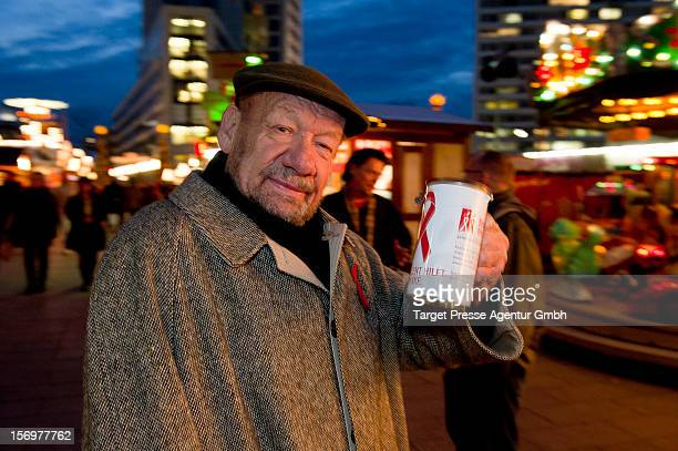Actor Wolfgang Voelz collects donations during the 'KartoffelpufferBratCharity' at the Berlin Christmas Market on November 26 2012 in Berlin Germany