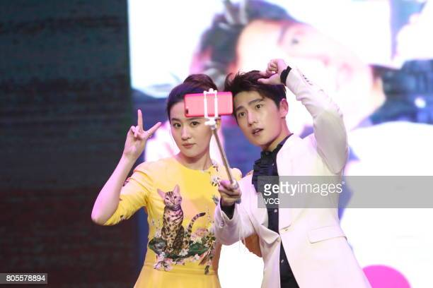 Actor Yang Yang and actress Liu Yifei take selfies during the press conference of film 'Once Upon a Time' on July 2 2017 in Beijing China