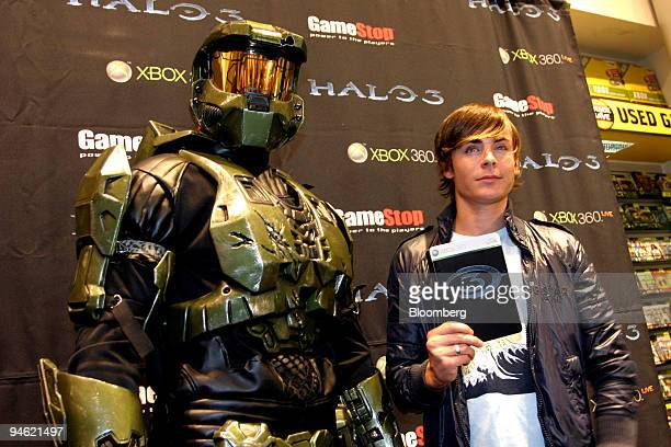 Actor Zac Efron poses with a character from the video game Halo 3 at a store in Universal City California on Tuesday Sept 25 2007 Microsoft Corp took...