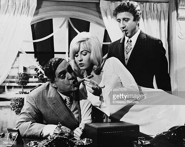 Actor Zero Mostel has his cigar lit by Lee Meredith as Gene Wilder looks on in a still from the film 'The Producers' directed by Mel Brooks 1968
