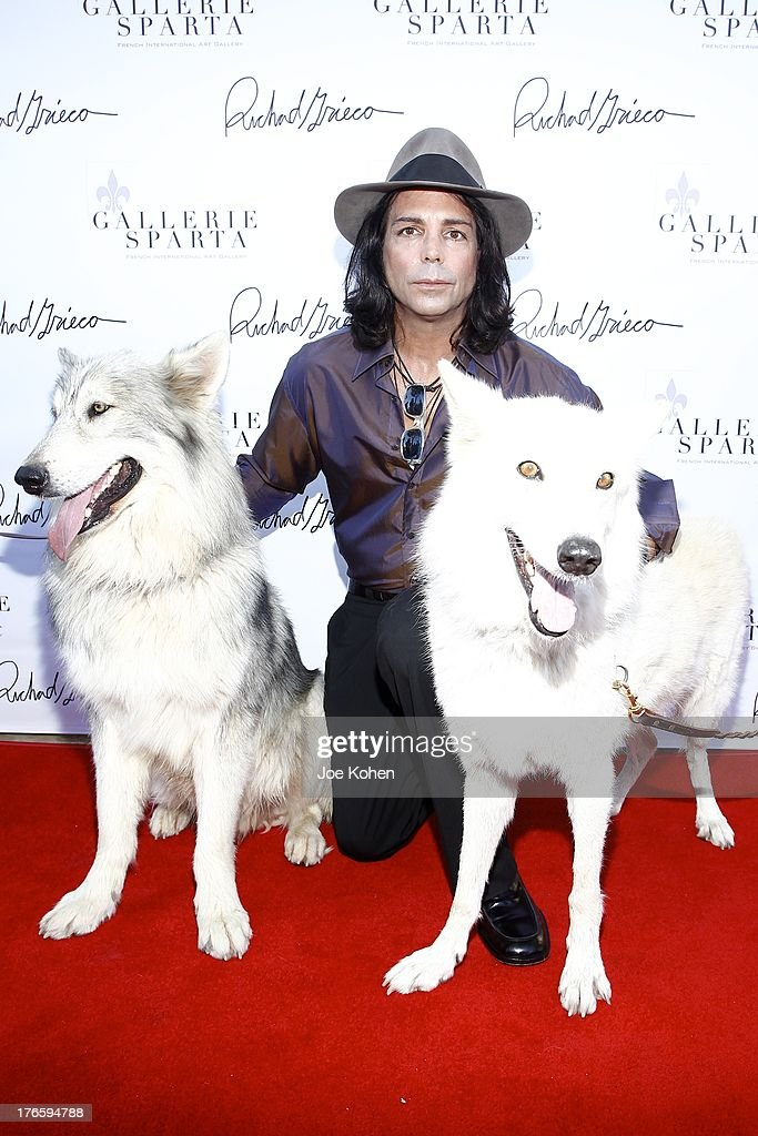 Actor/artist Richard Grieco poses for a photo with Ranger and Maya, wolfs from the Wolfconnection.org at Richard Grieco's opening night gala for his one-man art exhibit 'Sanctum Of A Dreamer!' at Gallerie Sparta on August 15, 2013 in West Hollywood, California.