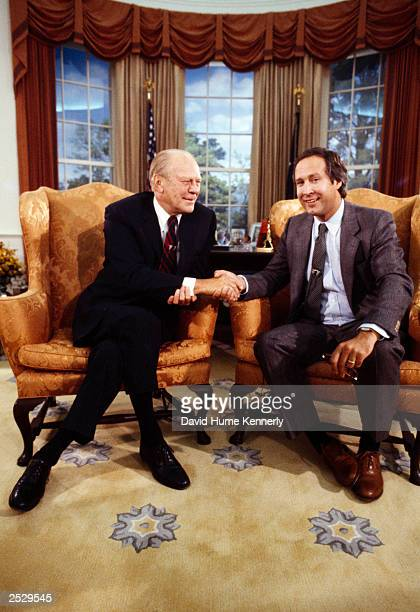Actor/comedian Chevy Chase shakes hands with former US President Gerald R Ford from a seat in the fullscale replica of the Oval Office furnished as...