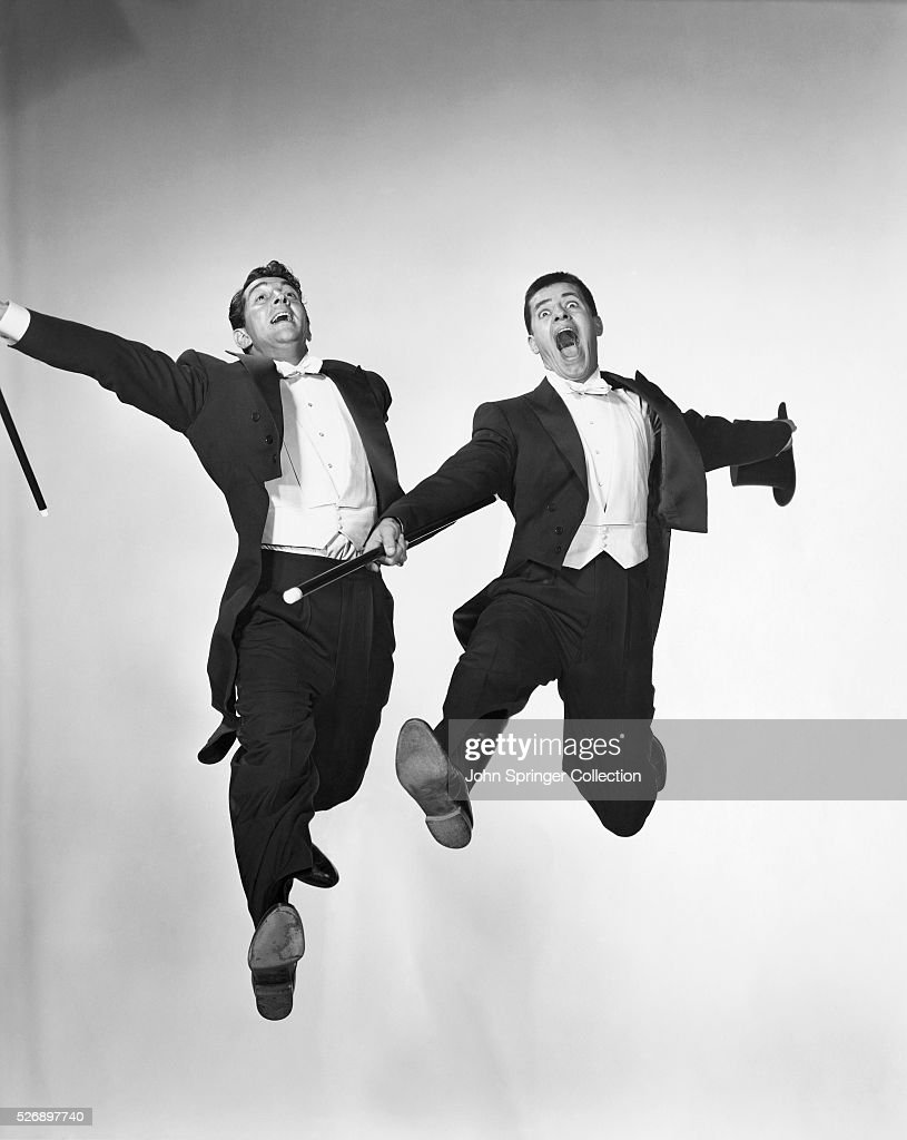 Actor/comedian Jerry Lewis and actor Dean Martin dressed in tuxedos. Moviestill shows them caught in a mid-air jump. Undated photograph.