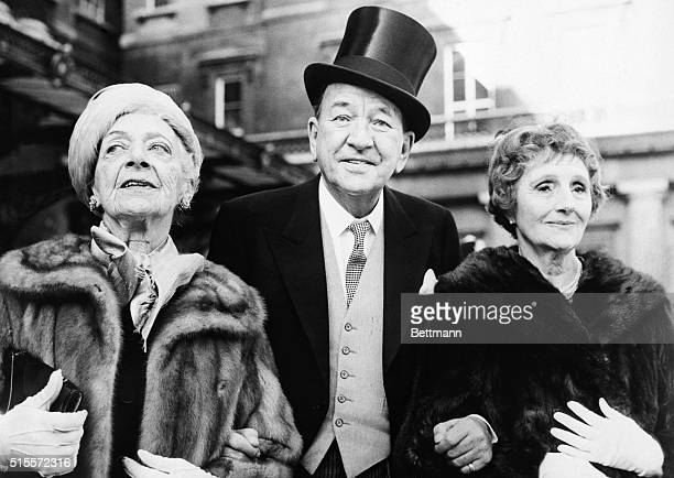 Actorplaywrightcomposer Sir Noel Coward accompanied by Mrs GE Calthorp and actress Joyce Carey leaves Buckingham Palace Feb 3rd after being knighted...