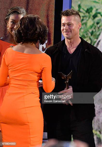 Actor/producer Brad Pitt accepts the Best Feature award for '12 Years a Slave' from actress Angela Bassett onstage during the 2014 Film Independent...