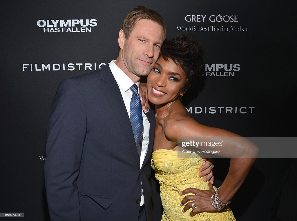 Actors Aaron Eckhart (L) and Angela Bassett arrive at the premiere of FilmDistrict's 'Olympus Has Fallen' at ArcLight Cinemas Cinerama Dome on March 18, 2013 in Hollywood, California.