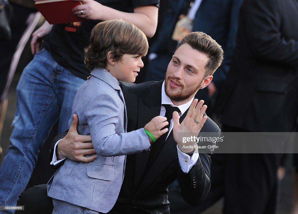 Actors Aaron Taylor-Johnson (R) and Carson Bolde arrive at the Los Angeles premiere of 'Godzilla' at Dolby Theatre on May 8, 2014 in Hollywood, California.