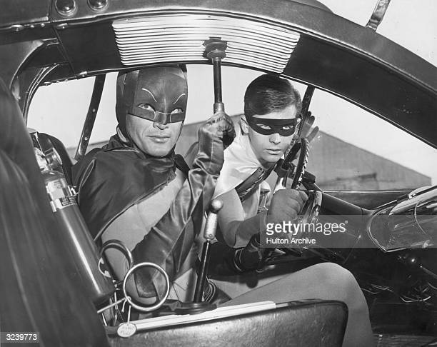 Actors Adam West and Burt Ward as Batman and Robin in the Batmobile in a still from the television series 'Batman'