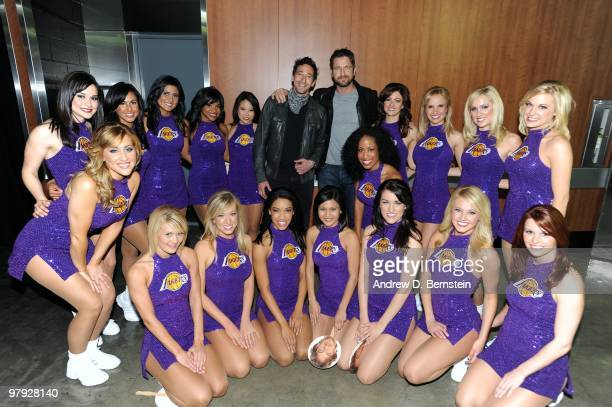 Actors Adrien Brody and Gerard Butler pose for a photograph with the Los Angeles Laker Girls following a game between the Washington Wizards and the...