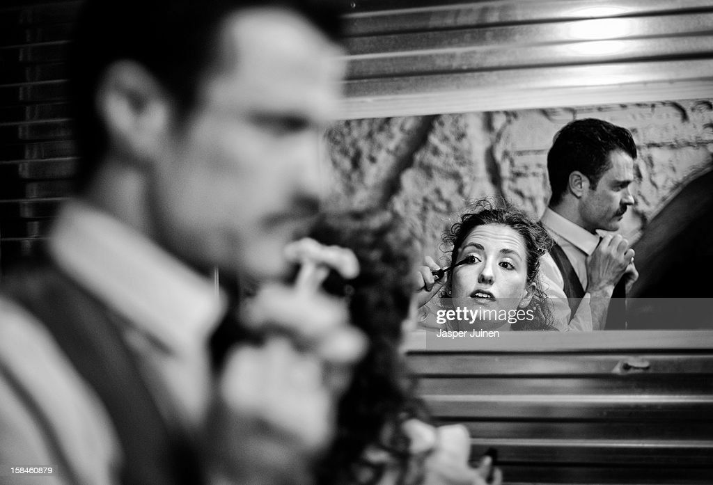 Actors Aitor Merino (L) and Cristina Ramos adjust their looks in between their 'Noche de bodas' micro theater shows at the 'Micro Teatro por Dinero' on December 15, 2012 in Madrid, Spain. In November 2009, fifty artists presented a theatre project in the thirteen rooms of a former brothel, two weeks before its demolition, with each function lasting less than 10 minutes. The initiative was a huge success, with more people queueing up outside than could enter. Today's 'Micro Theatre For Money' is named after the former brothel on Ballesta Street, and offers a cheap and original way for going out at night, especially in times of financial hardship. With each show priced at 4 Euros, over 150,000 spectators have already attended performances at the tiny theatre in the Malasana area. Anyone can submit a project to be chosen to perform for a month in one of the five tiny rooms in the basement of the theatre, making it an ideal platform for young Spanish authors and actors, often unemployed, to perform.