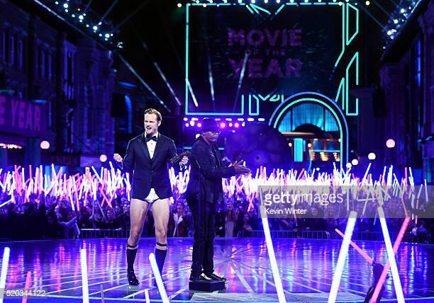Actors Alexander Skarsgard and Samuel L Jackson speak onstage as audience members wave lightsabers during the 2016 MTV Movie Awards at Warner Bros...