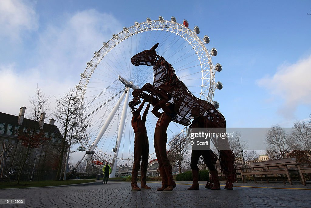 Actors and puppeteers from the West End production of the play 'War Horse' perform in front of the London Eye Ferris wheel to celebrate their 2000th performance on January 21, 2014 in London, England.
