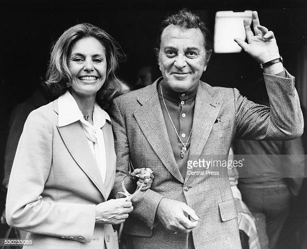Actors and spouses Cyd Charisse and Tony Martin waving as they arrive in London to star in a show at the London Palladium September 6th 1977