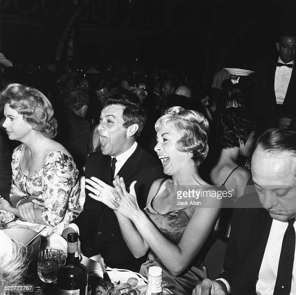Actors and spouses Tony Curtis and Janet Leigh laughing and clapping as they watch the opening night of Milton Berle at the Cocoanut Grove April 1960