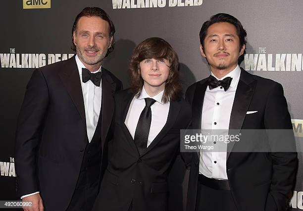 Actors Andrew Lincoln Chandler Riggs and Steven Yeun attend the season six premiere of 'The Walking Dead' at Madison Square Garden on October 9 2015...