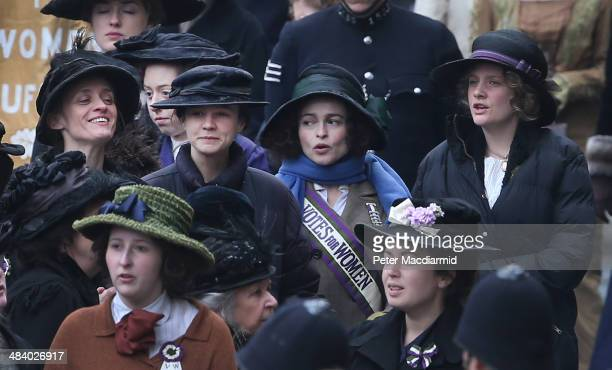 Actors AnneMarie Duff Carey Mulligan Helena Bonham Carter and Romola Garai keep warm during a break in filming of the movie Suffragette at Parliament...
