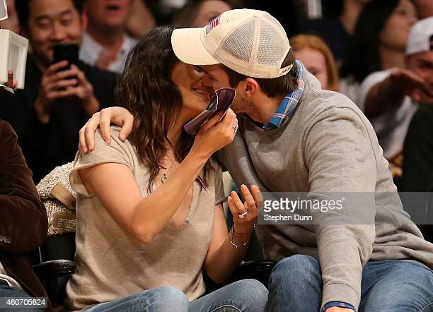 Actors Ashton Kucher and Mila Kunis kiss as they are shown on the video board during the 'kiss me camera' feature during the game between the...