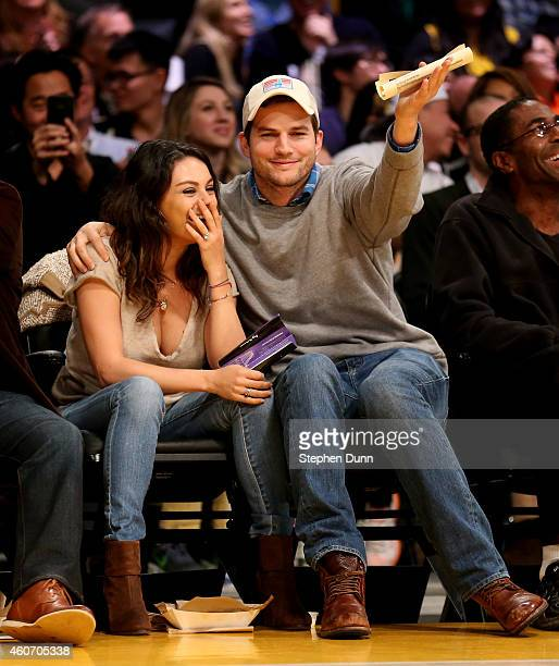 Actors Ashton Kucher and Mila Kunis react after being shown on the video board during the 'kiss me camera' feature during the game between the...