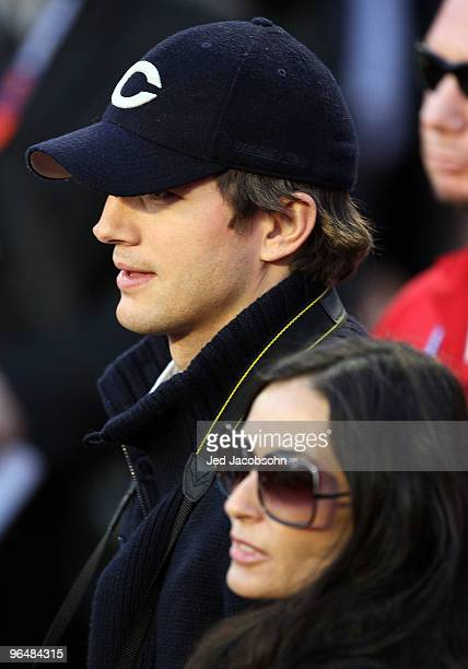 Actors Ashton Kutcher and Demi Moore pose on the sidelines prior to Super Bowl XLIV between the Indianapolis Colts and the New Orleans Saints on...