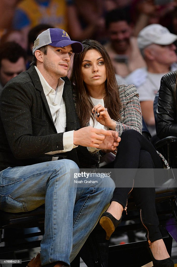 Actors Ashton Kutcher and Mila Kunis look on during a game between the New Orleans Pelicans and the Los Angeles Lakers at Staples Center on March 4, 2014 in Los Angeles, California.