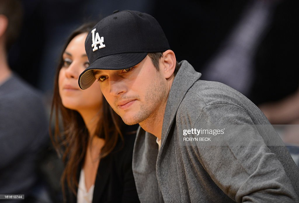 Actors Ashton Kutcher (R) and Mila Kunis (L) sit courtside at the Los Angeles Lakers NBA match up against the Phoenix Sun at Staples Center in Los Angeles, California, February 12, 2013. The Lakers defeated the Sun 91-85. Kobe Bryant finishes with only four points, nine assists and eight turnovers. AFP PHOTO / Robyn BECK