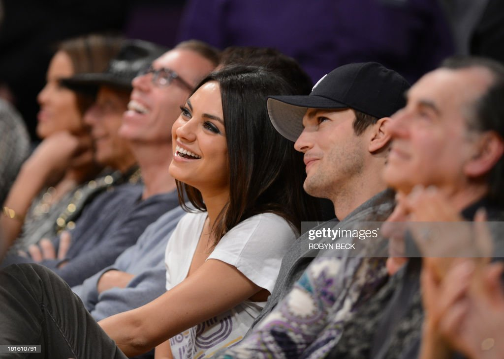 Actors Ashton Kutcher (R) and Mila Kunis (L) sit courtside at the Los Angeles Lakers NBA match up against the Phoenix Suns, at Staples Center in Los Angeles, California, February 12, 2013. The Lakers defeated the Suns, 91-85. Kobe Bryant finishes with only four points, nine assists and eight turnovers. AFP PHOTO Robyn BECK