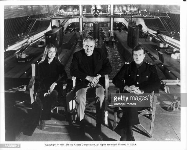Actors Barbara Bach and Roger Moore sitting in front of a submarine tank at Pinewood Studios with producer Albert R Broccoli between them during the...