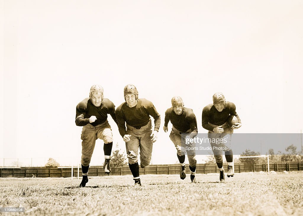 1940 Actors Bill Byrne, Nick Lukats, Kane Richmond and Bill Marshall from the film 'Knute Rockne, All American', running in formation towards the photographer.