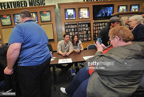 Actors Billy Flynn and Kate Mansi pose for pictures for one of their fans during the Days Of Our Lives book signing at the Oak Park Mall Barnes And...