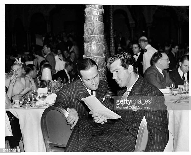 Actors Bob Hope and Fred MacMurray sit and look over a paper during an event in Los Angeles California