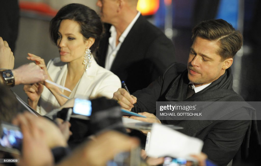 US actors <a gi-track='captionPersonalityLinkClicked' href=/galleries/search?phrase=Brad+Pitt+-+Actor&family=editorial&specificpeople=201682 ng-click='$event.stopPropagation()'>Brad Pitt</a> and <a gi-track='captionPersonalityLinkClicked' href=/galleries/search?phrase=Angelina+Jolie&family=editorial&specificpeople=201591 ng-click='$event.stopPropagation()'>Angelina Jolie</a> sign autographs on the red carpet for the German premiere of the film �The Curious Case of Benjamin Button� by US director David Fincher on January 19, 2009 in Berlin. The film is adapted from the 1920s story by F. Scott Fitzgerald about a man who is born in his eighties and ages backwards.