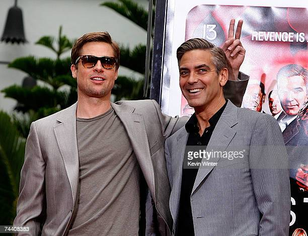 Actors Brad Pitt and George Clooney stars of the film Ocean's 13 pose for photos during their hand and footprints ceremony at Grauman's Chinese...