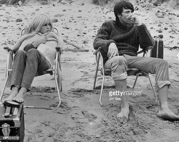 Actors Brigitte Bardot and Laurent Terzieff sitting on a cold beach during the filming of 'Two Weeks in September' Seacliffe Beach Scotland 1966
