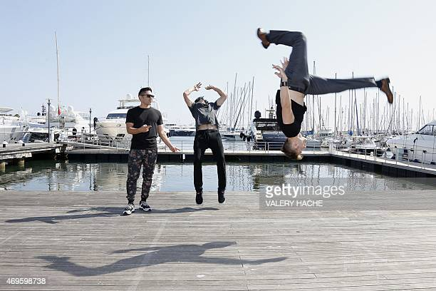Actors Caine Sinclair jumps along with William Spencer as Daniel 'Malakai' Cabrera looks on during a photocall for the serie 'The two bellmen' during...