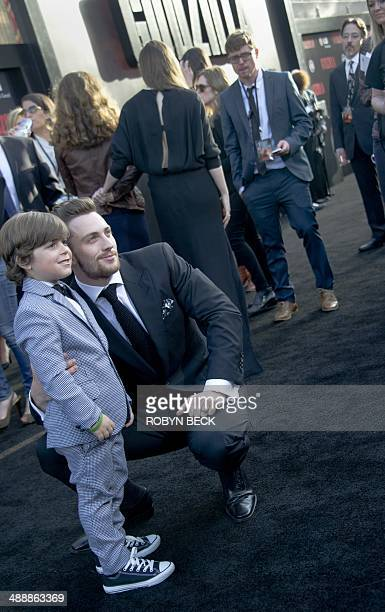 Actors Carson Bolde and Aaron TaylorJohnson pose together at the Los Angeles premiere of 'Godzilla' May 8 2014 at the Dolby Theatre in Hollywood...