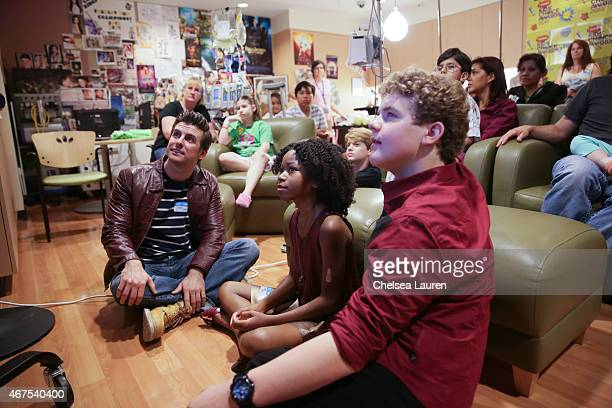 Actors Cooper Barnes Riele Downs Jace Norman and Sean Ryan Fox watch cartoons with children as they bring the Kids Choice Awards experience to...